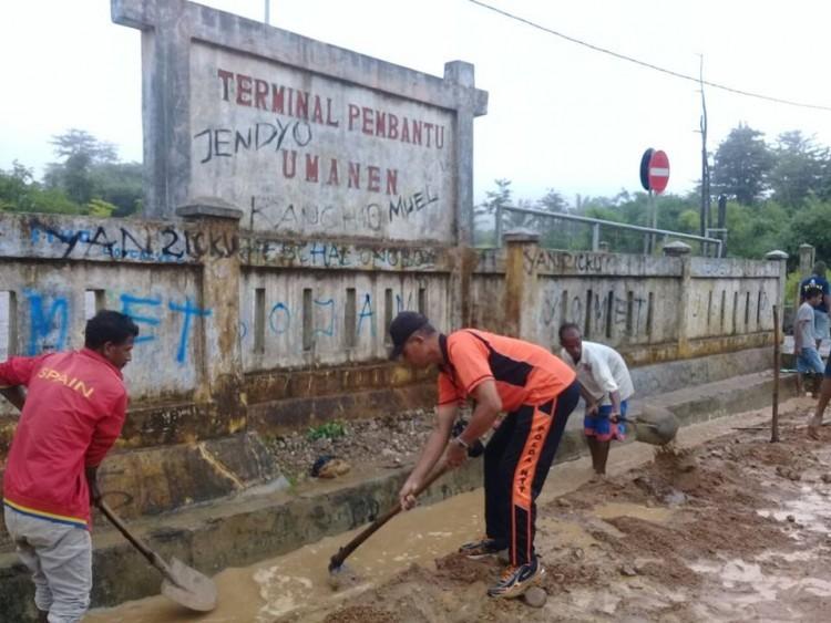 Bergelut dengan Lumpur, Bhabinkamtibmas Umanen Polres Bersihkan Saluran Air di Terminal Sesekoe