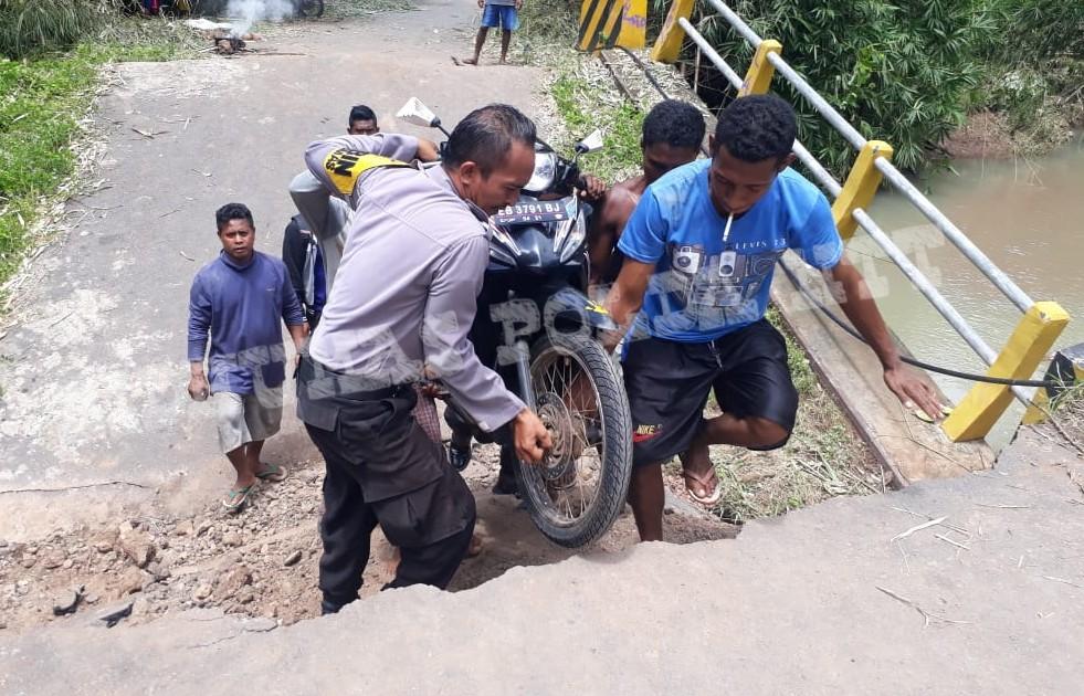 Aksi Heroik Brigpol Soalihin Membantu Mengangkat Sepeda Motor Warga yang Melintasi Jembatan Wailamung